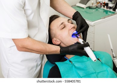 Dentist shine a bright blue Light in the male patient's mouth to harden composite filling. Dental treatment process