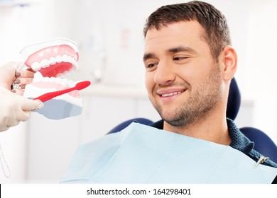 Dentist showing to man patient on mockup how to clean teeth