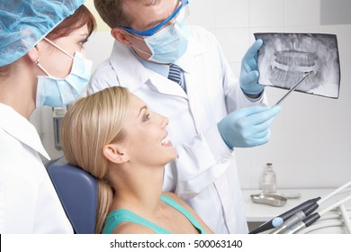A dentist showing a patient her teeth x-ray