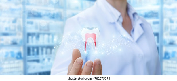 Dentist showing tooth model on blurred background.