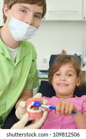 Dentist shows to patient girl how to correctly brush teeth. For clarity, doctor uses an artificial jaw. Focus on doctor.