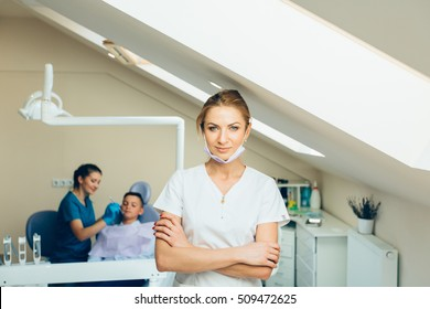 Dentist standing near the dental chair and look at the camera