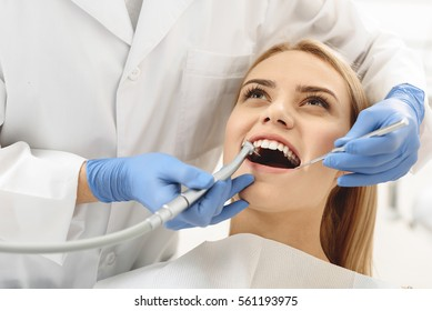 Dentist starting common operation of cleaning female mouth