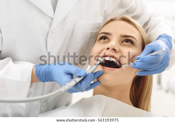 Zahnärzte, die eine gemeinsame Tätigkeit zur Reinigung der weiblichen Mundschleimhaut beginnen