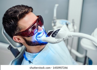 Photo of Dentist starting teeth whitening procedure with young man.