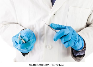 a dentist with surgical gloves and lab coat holding dental instruments