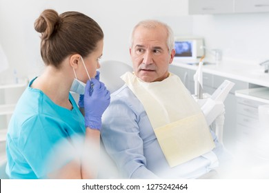Dentist talking to surprised senior patient sitting at dental clinic