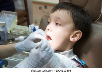 Dentist is treating a boy's teeth