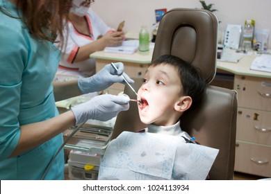 Dentist is treating a boy's teeth