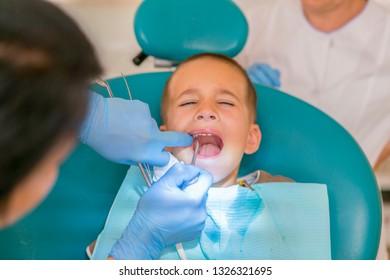 Dentist is treating a boy's teeth. Dentist examining boy's teeth in clinic. A small patient in the dental chair smiles. Dantist treats teeth