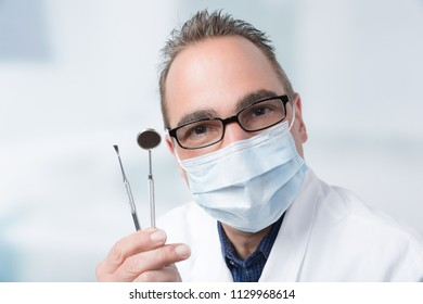 dentist with two dental instruments