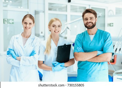 A dentist and two nurses are posing in the dental office on the background of dental equipment. Happy dentist concept.
