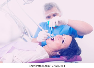 dentist in uniform health tooth visitor in dentist's chair in the room