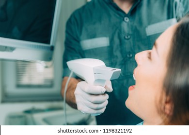 Dentist using dental camera, scanning the teeth. Beautiful female patient