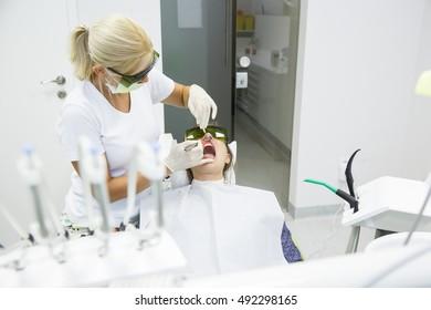 Dentist using a modern diode dental laser for periodontal care. Both wearing protective glasses, preventing eyesight damage. Periodontitis, dental hygiene, preventive procedures concept.