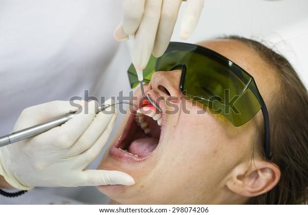 Dentist using a modern diode dental laser for periodontal care. Patient wearing protective glasses, preventing eyesight damage. Periodontitis, dental hygiene, preventive procedures concept.Ã?Â??