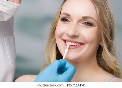 dentist using shade guide at woman's mouth to check veneer of tooth