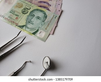 dentist utensils for oral review and singaporean banknotes