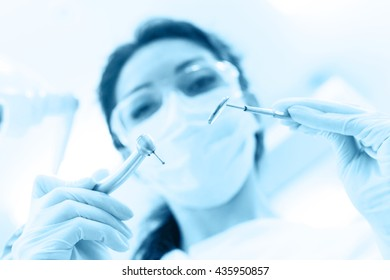 Dentist wearing surgical mask while holding angled mirror and drill, ready to begin