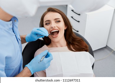 Dentist working with patient at light medical background, modern clinic, dental clinic, healthy teeth, satisfied client, portrait.