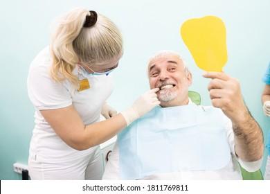 Zahnarztkonzept. Professioneller Zahnarztservice und moderne Ausrüstung ohne Schmerzen. Ein Arzt berät und behandelt einen älteren Mann. Der Patient schaut in den Spiegel