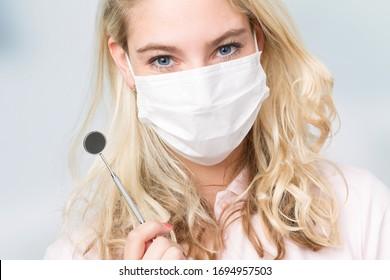 dentist's assistant or female dentist with dental face mask shows dental instrument