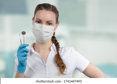dentist's assistant or female dentist with dental face mask presenting dental instruments in front of a dentistry room