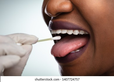 Dentist's Hand Taking Saliva Test From Woman's Mouth With Cotton Swab