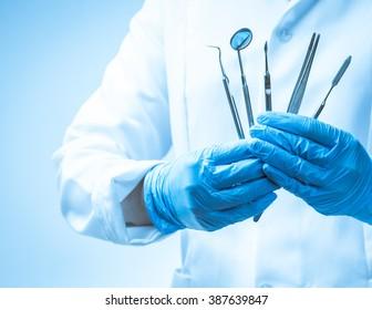 Dentist's hands holding dental tools