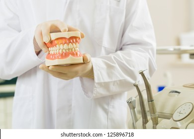 Dentists in his surgery holds a denture, in the background are tools for a dentist