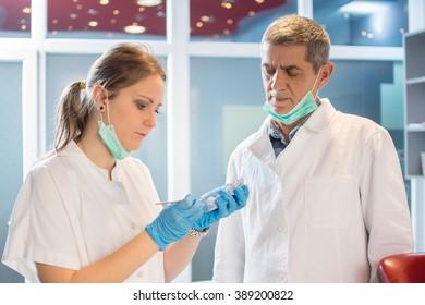 Dentists looking at  plaster model in dental office.