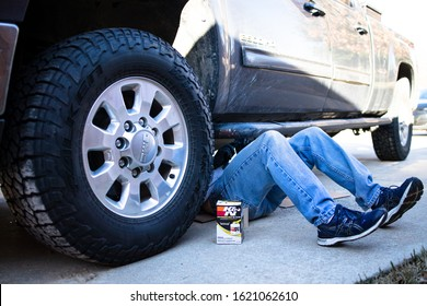 Denton, TX / USA - January 19, 2020: Man lying under a GMC 3/4 ton diesel truck changing the K&N Oil Filter in the course of a do-it-yourself at home oil change