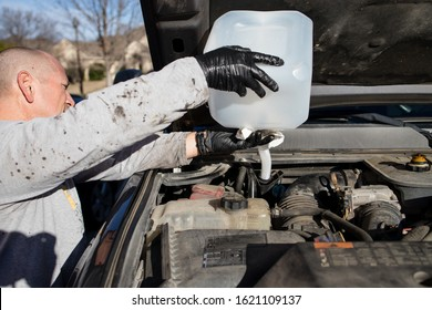 Denton, TX / USA - January 19, 2020: Side view of Man pouring diesel engine fluid into a diesel truck, part of DIY auto maintenance. The fluid helps reduce the air pollution caused by diesel engines.