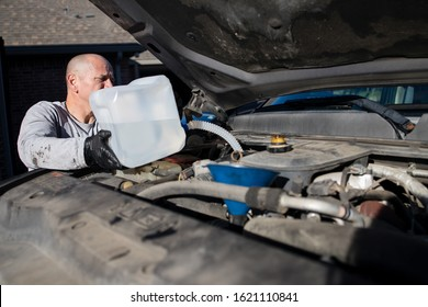 Denton, TX / USA - January 19, 2020: Front view of man pouring diesel engine fluid into a diesel truck, part of DIY auto maintenance. Blu DEF helps reduce the air pollution caused by diesel engines.