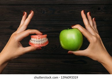Denture and Apple in the hands of a doctor. False teeth denture against green granny smith apple. Dental prosthesis care. Dental care. Beautiful tooth. Prosthetics. False teeth
