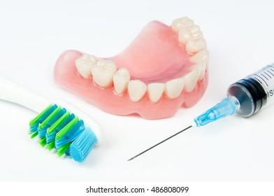 Denture brush and syringe on white background