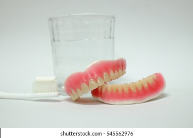 denture, glass of water and toothbrush for cleaning on white background (isolated)