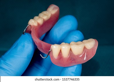 denture. Partial removable denture of the lower jaw of a person with white beautiful teeth in the hand of dentist. Aesthetic Dentistry