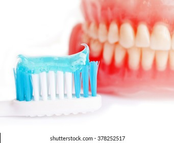Denture and tooth paste isolated on white