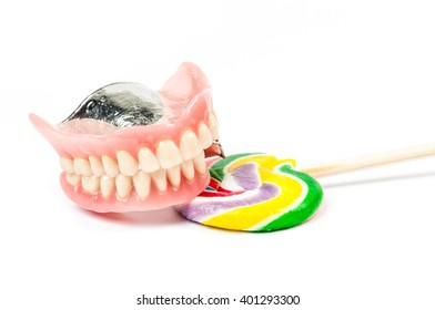 Dentures with colorful lollipop on white background