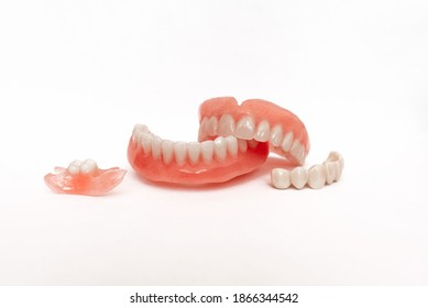 Dentures on a white background. Close-up of dentures. Full removable plastic denture of the jaws. Prosthetic dentistry. False teeth. Close-up of plastic dentures. Teeth on a white background
