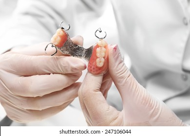 Dentures, oral hygiene.Prosthetics hands while working on the denture, false teeth, a study and a table with dental tools.