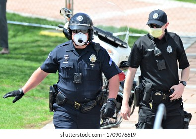 Denver, CO, USA, April 19, 2020.  Denver Police wearing face masks monitored the Stay at Home peaceful protest at the Denver, Capital. They mostly directed traffic and kept everyone safe.