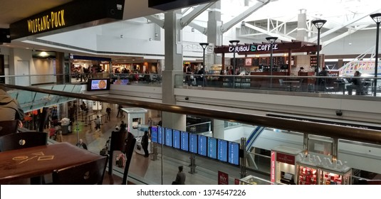 Denver, CO, USA - February 21, 2019 - Denver International Airport Concourse B with flight status screens and food businesses in the background
