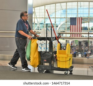 Denver, CO, USA. July 27, 2019. Janitorial staff member pushing his cleaning cart around Denver International Airport on a very busy Saturday morning.