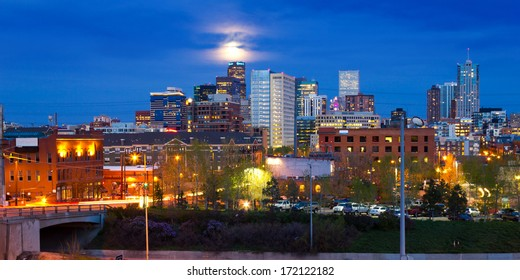 Denver, Colorado colorful panoramic skyline with full moon rising at dusk