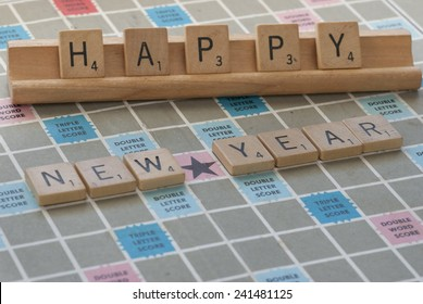 """Denver, Colorado - December 31, 2014:  """"Happy New Year"""" concept spelled out in wooden Scrabble letters on wooden rack and Scrabble game  board"""
