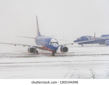 DENVER, COLORADO: JANUARY 24, 2019: Southwest plane on runway as second one passes behind in snow storm