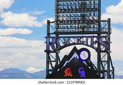 Denver, Colorado - June 23, 2018: closeup of Colorado Rockies sign with rocky mountains in backgroud