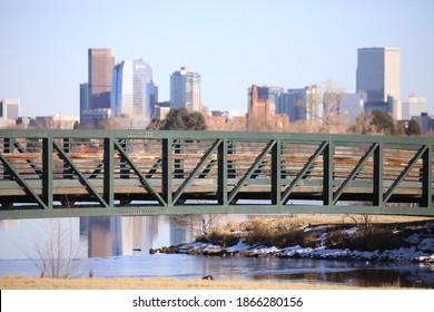 DENVER, COLORADO - NOVEMBER 30, 2020: Walking Bridge Over Sloan Lake With Denver Downtown In Background